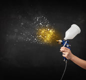 Worker with airbrush painting with glowing golden paint Royalty Free Stock Images