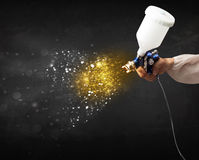 Worker with airbrush painting with glowing golden paint Stock Photo