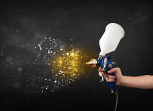 Worker with airbrush painting with glowing golden paint Stock Photos