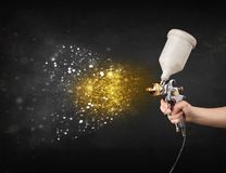 Worker with airbrush painting with glowing golden paint. And particles Royalty Free Stock Photos