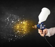 Worker with airbrush painting with glowing golden paint. And particles Stock Photos