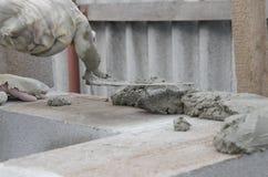 Worker aligns with a spatula, lay brick cinderblocks.  Stock Photos