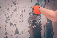 The worker aligns the wall. With a tile adhesive applying it with a spatula, preparation for tiling royalty free stock photography