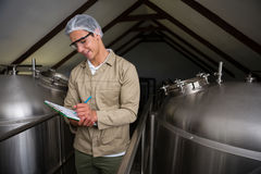 Worker amidst storage tanks writing on clipboard at brewery Stock Images