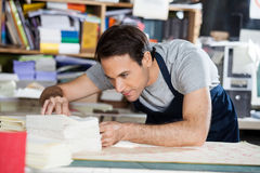 Worker Analyzing Papers At Workbench In Factory Stock Photography