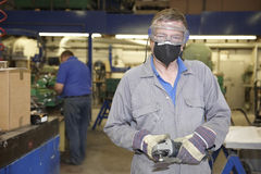 Worker with angle grinder. Factory floor worker holding a angle grinder and looking at camera Royalty Free Stock Photo