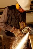 Worker with angle grinder. An helmet and protectors Royalty Free Stock Image