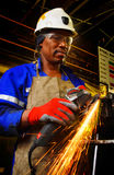 Worker and angle grinder. An African Worker with safety gear cutting steel with angle grinder Royalty Free Stock Photo