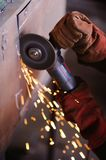 Worker with angle grinder. Sparks from welding or from a torch for metal Royalty Free Stock Images