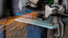 Worker with angular grinding machine is cutting the metal stock video