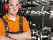 Worker with antiphons and protection glasses  in front of production machine Royalty Free Stock Image