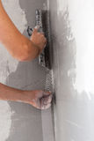 Worker applied with a spatula to a solution of fiberglass mesh Stock Photo