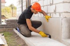 Bitumen waterproofing of the foundation. Worker applies bitumen mastic on the foundation stock photography