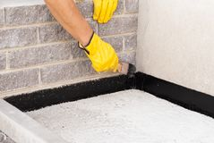 Bitumen waterproofing of the foundation. Worker applies bitumen mastic on the foundation royalty free stock photos