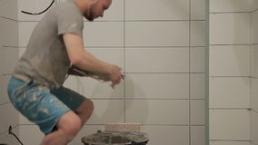 Worker applies cement to tile and puts her to wall indoors. stock footage