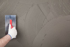 The worker applies glue for a tile on a wall Royalty Free Stock Photo