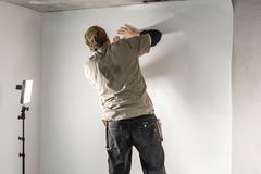 Worker applies a sheet of Wallpaper. Man glueing wallpapers on concrete wall. Repair the apartment. Home renovation. Young man, worker glueing wallpapers on stock photography