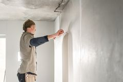Worker applies a sheet of Wallpaper. Man glueing wallpapers on concrete wall. Repair the apartment. Home renovation. Young man, worker glueing wallpapers on royalty free stock photography
