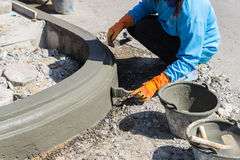 The worker apply cement over the surface of footpath edge Stock Photography