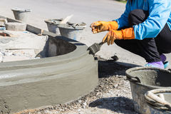 The worker apply cement over the surface of footpath edge Stock Photo