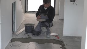 Worker apply glue adhesive on floor and lay hexagon tiles