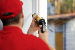 Worker applying caulk around window frame. Worker in red uniform applying caulk around window frame Stock Photos