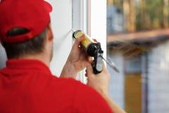 Worker applying caulk around window frame. Worker in red uniform applying caulk around window frame stock photos
