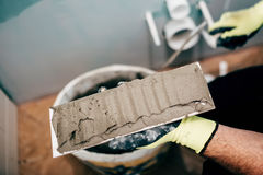 Worker applying mortar on ceramic tiles and working on rebuilding a bathroom Royalty Free Stock Image