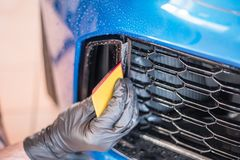 Worker is applying paint protection film with squeegee on car buffer. Paint protection a thermoplastic urethane often self healing film applied to painted royalty free stock photography