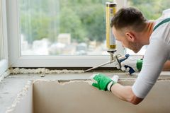 Worker is applying polyurethane foam. To fill gap between sash and window frame. Creating comfort and coziness for your home royalty free stock images