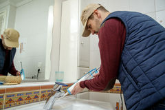 Worker applying silicone sealant in the bathroom. Royalty Free Stock Images