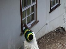 A worker applying varnish at a house in the cairbbean. Maintaining woodwork on windowsills in the tropics stock footage