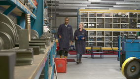 Worker And Apprentice Checking Stock Levels In Store Room stock video