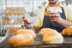 Worker in apron holding box and bread Royalty Free Stock Photos