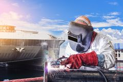 Welding infactory. Worker arc welder piping welding double exposure concept in shipyard on monotone and ship background Stock Image