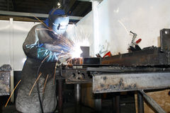 Worker arc welding. Sparks flying from a factory artisan wearing protective gear while welding metal Royalty Free Stock Photo