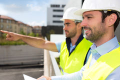 Worker and architect watching some details on a construction Royalty Free Stock Photo