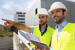 Worker and architect watching some details on a construction Stock Image