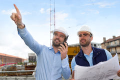 Worker and architect watching some details on a construction Stock Photos