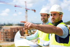 Worker and architect watching some details on a construction Stock Images