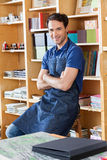 Worker With Arms Crossed Sitting In Book Store Stock Photo