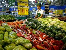 A worker arranges fresh fruits and vegetables on a shelf at a grocery store in Antipolo City. Royalty Free Stock Image