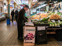 Worker arranges organic produce at Pike Place Public Market, Sea Stock Photos