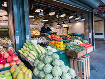 Worker arranges produce at shop in Pike Place, Seattle Royalty Free Stock Image