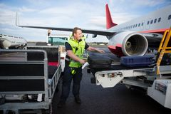 Worker Arranging Luggage On Trailer Connected To Airplane. Mid adult worker arranging luggage on trailer from conveyor connected to airplane on runway royalty free stock images