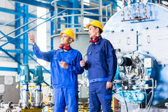 Worker in Asian manufacturing plant. Discussing in front of machines royalty free stock photo