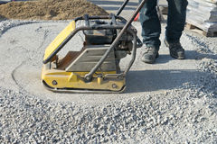 Worker With Asphalt Plate Tamper, Patio Home Improvement. A worker is using an asphalt plate tamper as he packs down crushed stone to create a base for a patio stock image