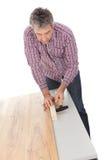 Worker assembling laminate floor Stock Images