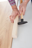 Worker assembling laminate floor. Using a hammer stock photography