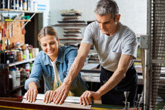 Worker Assisting Colleague To Use Squeegee Stock Photo
